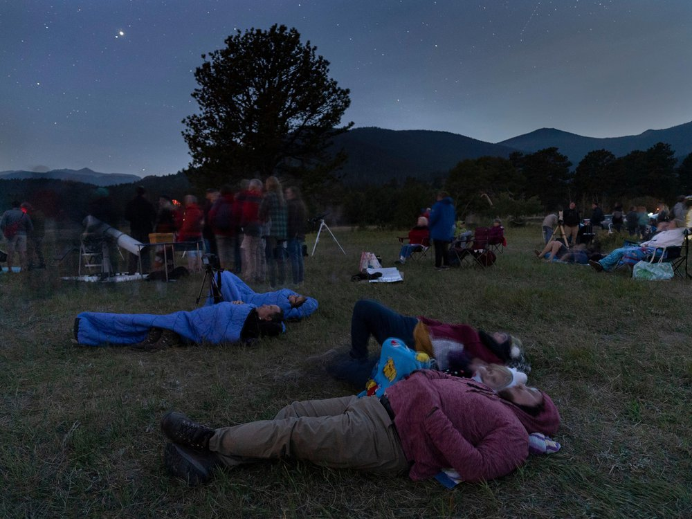 A crowd of people are laying on the ground in a grassy field at night with mountains in the background
