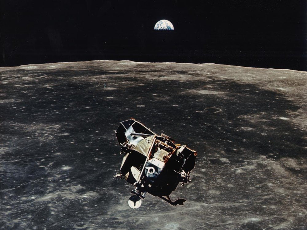 Apollo 11 ascent stage aloft above Earth with the moon rising in the distance