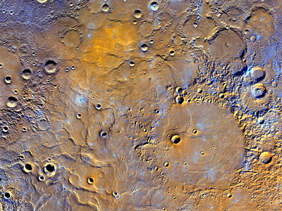 Mercury's northern volcanic plains shown in enhanced color to emphasize rocks types. The bottom left portion of the image displays large wrinkle ridges, formed during lava cooling. Near the top of the image, a bright orange region shows the location of a volcanic vent.
