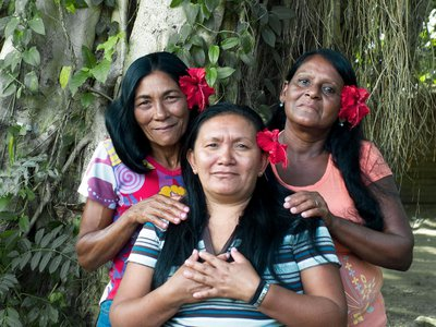Three Taíno Indian sisters pose during a family pig roast in eastern Cuba, where there's a small but growing movement to explore the indigenous culture that Columbus encountered in 1492.