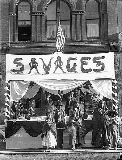 American Indians posed in front of a booth with sign advertising SAVAGES