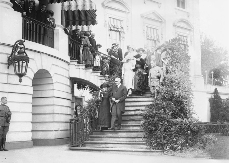 Black and white photo of Curie and President Harding on the White House steps