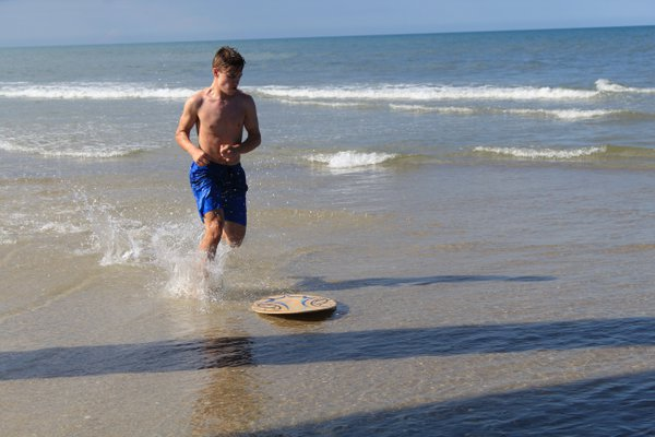 Skim boarder running after his board thumbnail