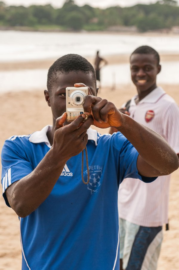 I was walking along the beach of Freetown, Sierra Leone, taking pictures when this young man, laughing, took a picture of me as I took pictures. He posed to return the favor, and I shot him taking my  thumbnail