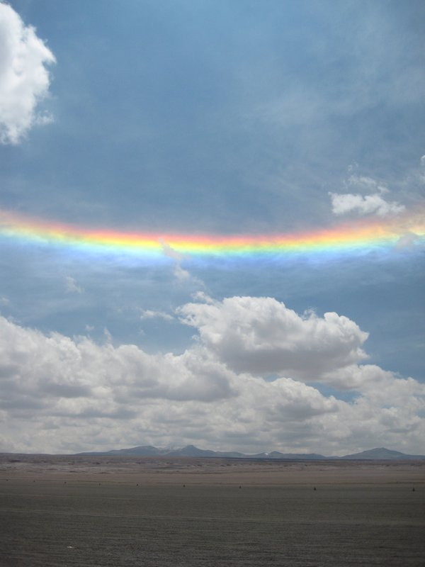 The bottom of two rainbows wholly encircling the sun rests above earth in Salar de Uyuni, Bolivia. thumbnail