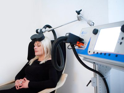 In transcranial magnetic stimulation, a magnetic device placed near the skull delivers painless pulses to the brain.