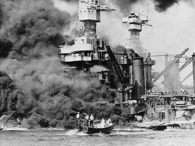 A small boat rescues a seaman from the 31,800 ton USS West Virginia burning in the foreground. Smoke rolling out amidships shows where the most extensive damage occurred.