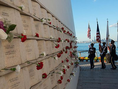 """On the inner wall of one of the two """"wings"""" comprising Masayuki Sono's Postcards monument in Staten Island, flowers are placed next to the names of victims of the 9/11 attacks."""
