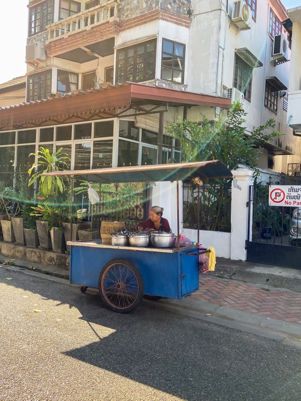 An elderly woman sells food in a quiet street in Vientiane thumbnail