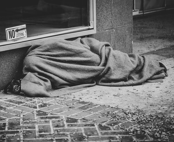 Homeless person covered up in a blanket to keep warm thumbnail