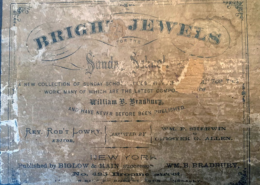 Worn cover of a book, titled Bright Jewels for the Sunday School. Rev. Rob't Lowry, Editor.