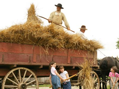 Young guests and living history staffers unload hay.