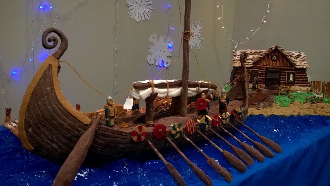 Brown, chocolate recreation of a viking ship complete with oars docked near a brown, chocolate cake recreation of a viking home on display on a rectangular table with a blue tablecloth.