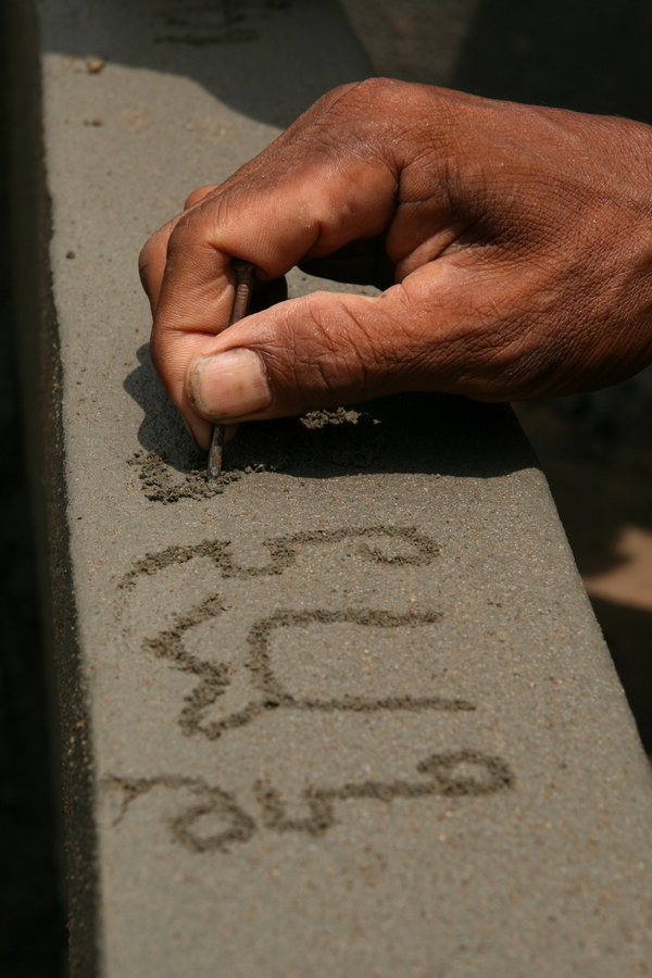 A man carves out his name in Khmer on a well he helped construct thumbnail