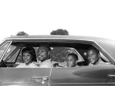 1960s family sitting in four-door sedan automobile