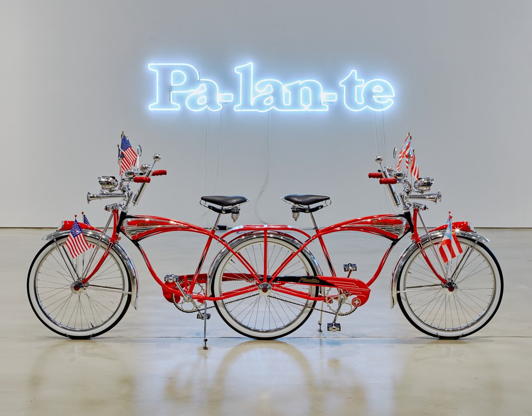 """A sculpture of a red bike. It has two front ends, joined together in the back. Above it, a neon light scuplture says """"Pa-lan-te."""""""