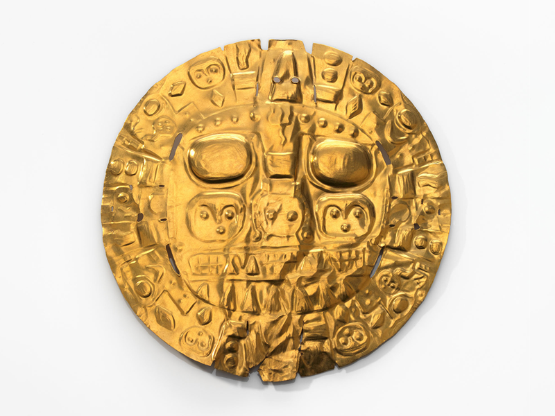 Against a white background, a shiny golden disc with raised features that depict two large, rounded eyes, the suggestion of a kind of face, and many interlocking diamonds, circles, lines and curved shapes