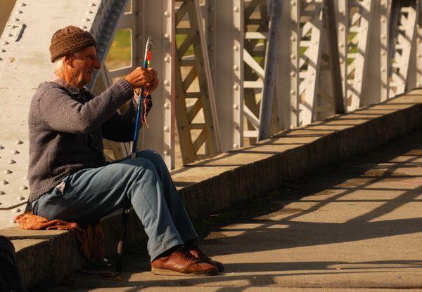An old man fishing on bridge thumbnail