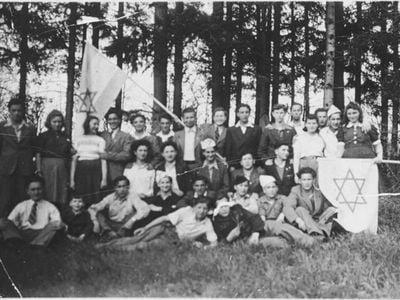 Group with flags in the forest: Michael Walter, Miklos Roth, Szlama Weichselblatt, Avram Leder, Halina Bryks, Naftali Steinberg, Roman Kniker, Jakob Kahan