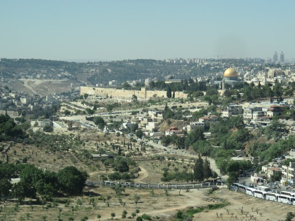 The golden Dome of the Rock mosque sits beyond the Old City walls, with the modern City of David and ancient Mount of Olives in the foreground. thumbnail