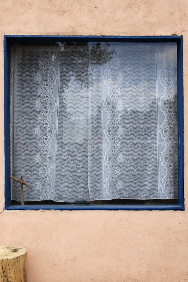 A curtained window on a pinkish building thumbnail