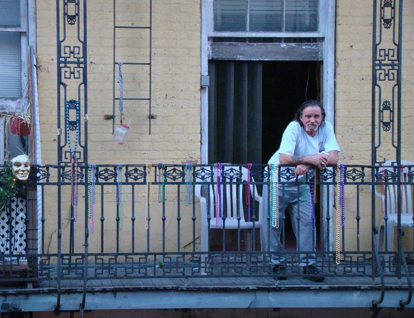 A man stands serenely above Bourbon St. on Fat Tuesday in New Orleans. thumbnail