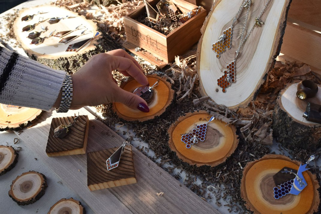 Several necklaces with honeycomb motifs are displayed on small, circular pieces of wood.
