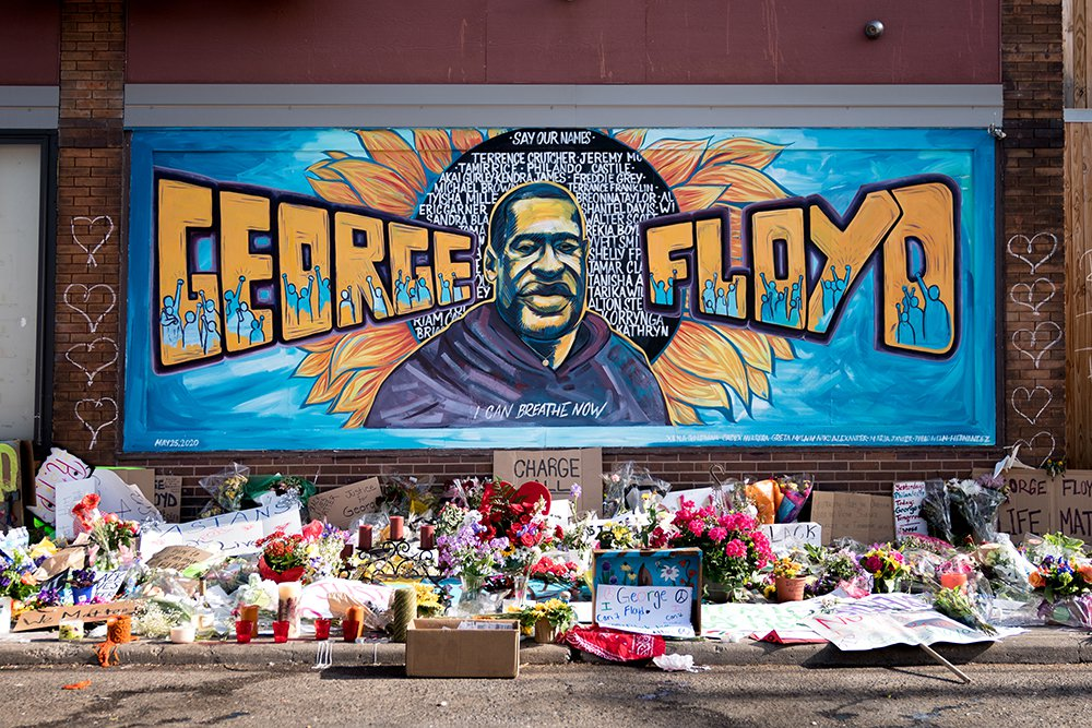 Large mural on a brick wall the words George Floyd in yellow letters against a blue background and a portrait of a man in the center against a sunflower with names listed in white lettering. There are white hearts drawn on the side of the mural and flowe