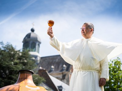 Father Karel Stautemas raising a glass of Grimbergen beer