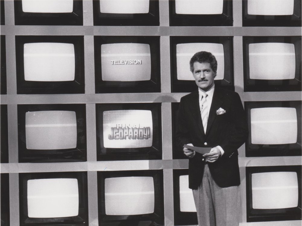 A black and white image of a young Trebek, a white man in a suit and tie with dark hair and a mustache, standing in front of a grid of TV screens