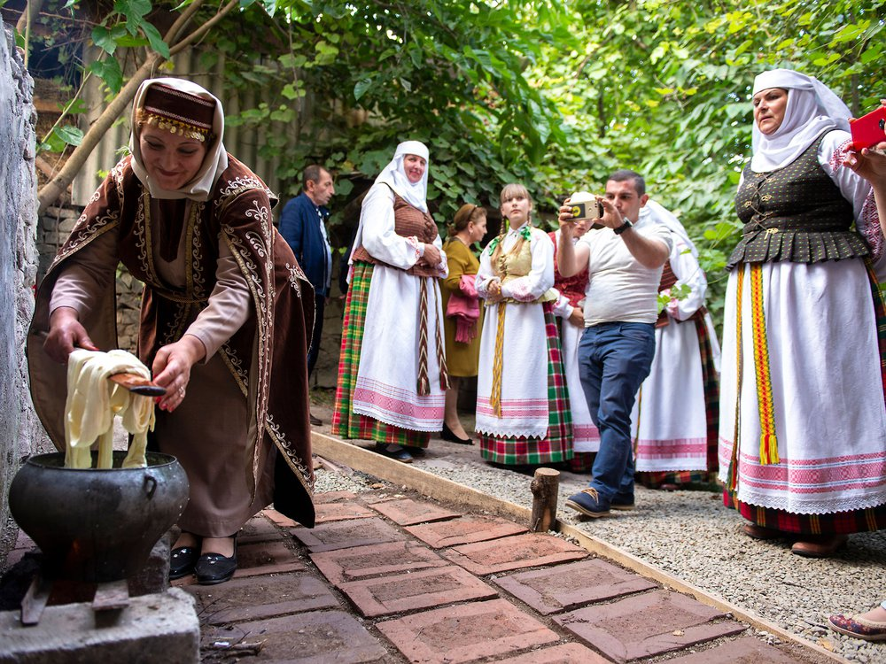 A woman wearing traditional Armenian dress bends down to tend to an outdoor stove while preparing a meal.