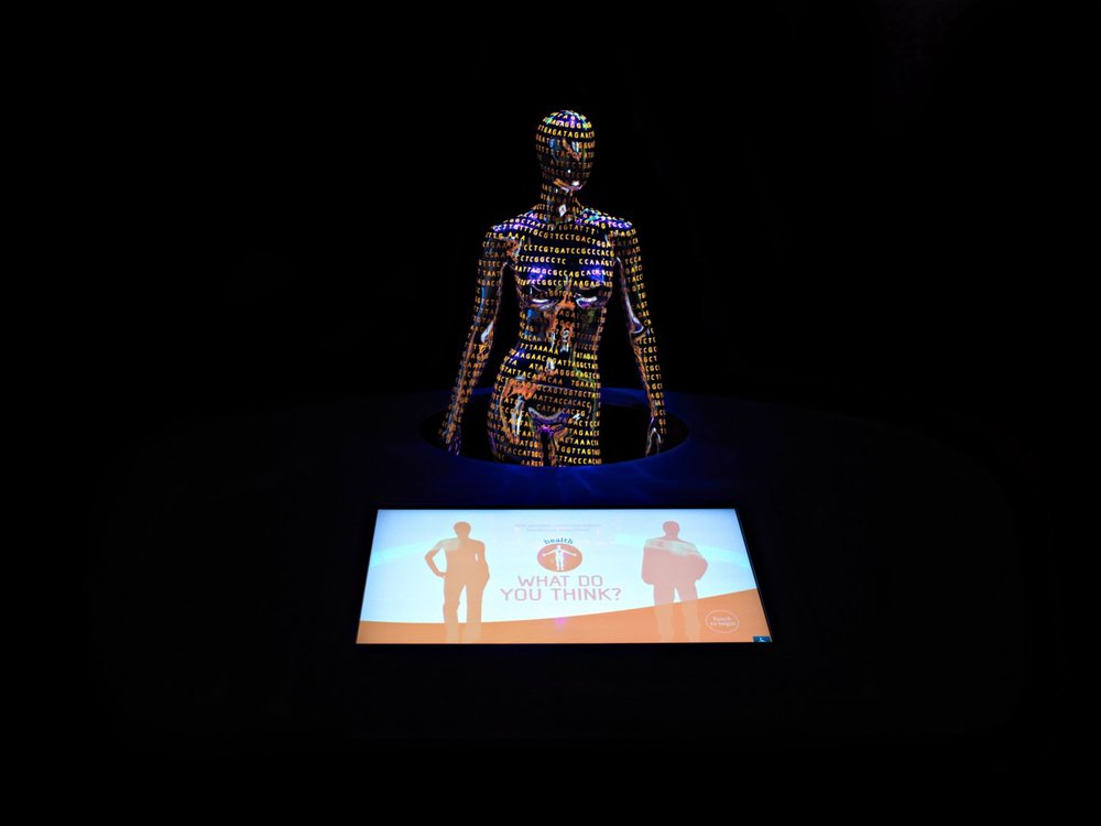 """A wide shot of a museum exhibit, featuring a dark, faceless, naked female mannequin covered in orange genetic code in the background with a monitor in the foreground showing an orange and white graphic of two people with """"What do you think?"""" between them."""
