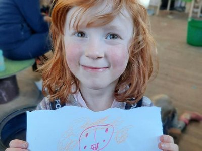 Five-year-old Astrid Cooper poses with one of her artworks. Astrid co-curated an upcoming exhibition at the Edge arts center in Bath, England, with her father, Will.