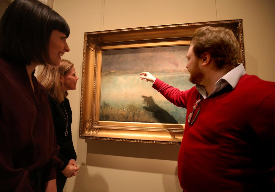 A photograph of three people standing in front of a painting of Niagara Fall. One of them is pointing towards the center.