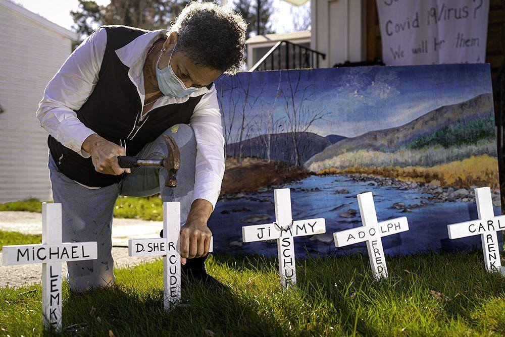 Julia Santos Solomon inserting crosses for her In Memoriam installation, Christ Lutheran Church, Woodstock, NY, 2020. Photo by Scott Barfield.