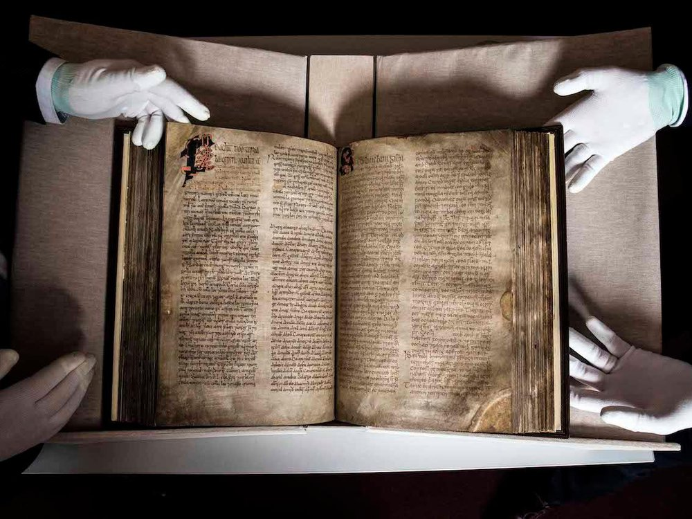 An aerial view of the book, which is spread out on a table, displaying its ornate text. Two pairs of white-gloved hands hold the book on either side