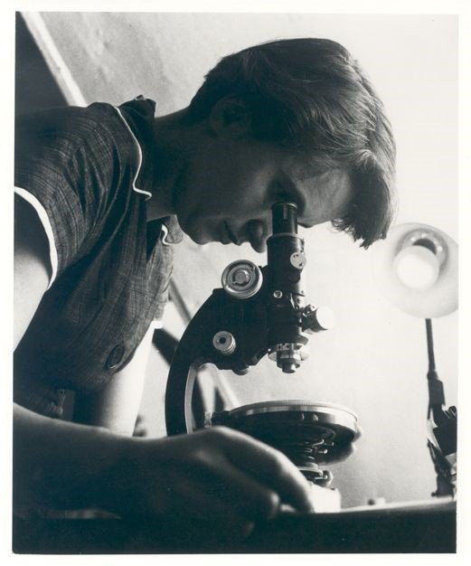 Black and white photo of a woman looking into a microscope.