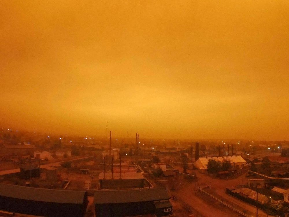 A photo of a small town in Russia. Its skies glowing an eerie amber color as wildfires continue to rage in Yakutia.