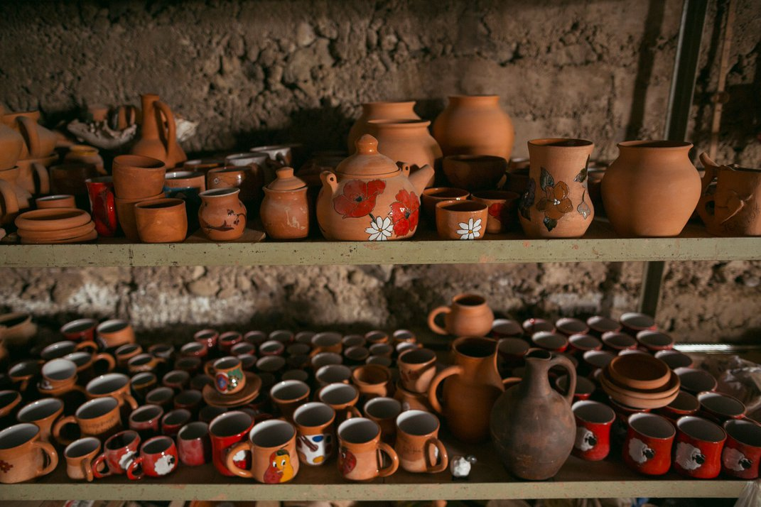 Several rows of teracotta pots are arranged on two shelves, one on top of the other.