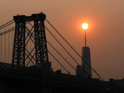 The sun sets behind the Manhattan Bridge and One World Trade Center in a haze created by smoke from the west coast wildfires reaching the east coast on September 15, 2020 in New York City, according to Getty Images.