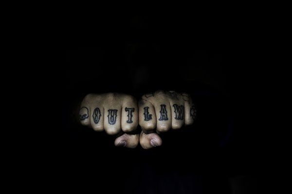 "Tattooed knuckles reading ""outlaw"" thumbnail"
