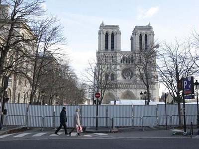 A couple passes by the fence in front of Notre-Dame in Paris on December 24, 2019.