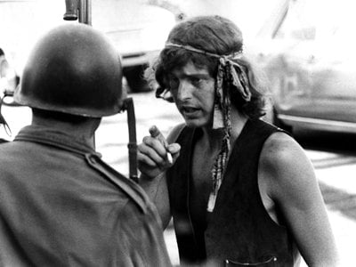 A man smokes a cigarette as he talks to an armored guard at a protest in People's Park circa May, 1969, in Berkeley, California.