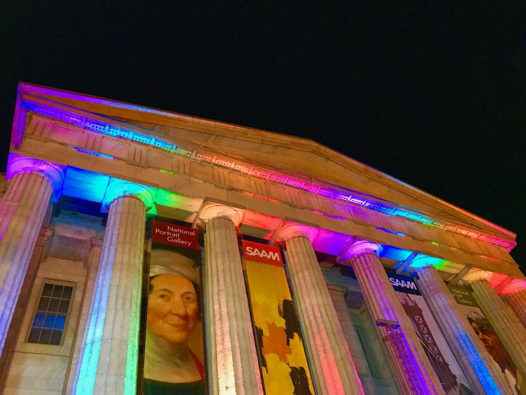 A photograph of the exterior of the Smithsonian American Art Museum at night with rainbow lights.
