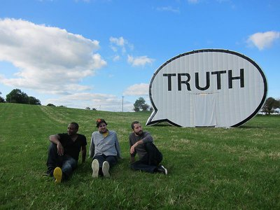 Artists Hank Willis Thomas, Jim Ricks and Ryan Alexiev pose in front of The Truth Booth at a stop in Ireland.