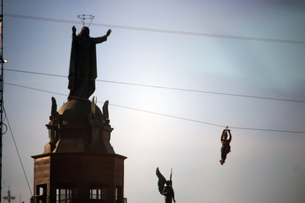 A person travels on a zipline past a statue in Montreal. thumbnail