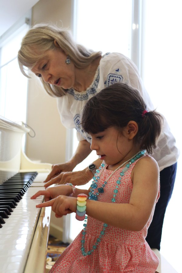 A grandma teaches her granddaughter to play Chopsticks. thumbnail
