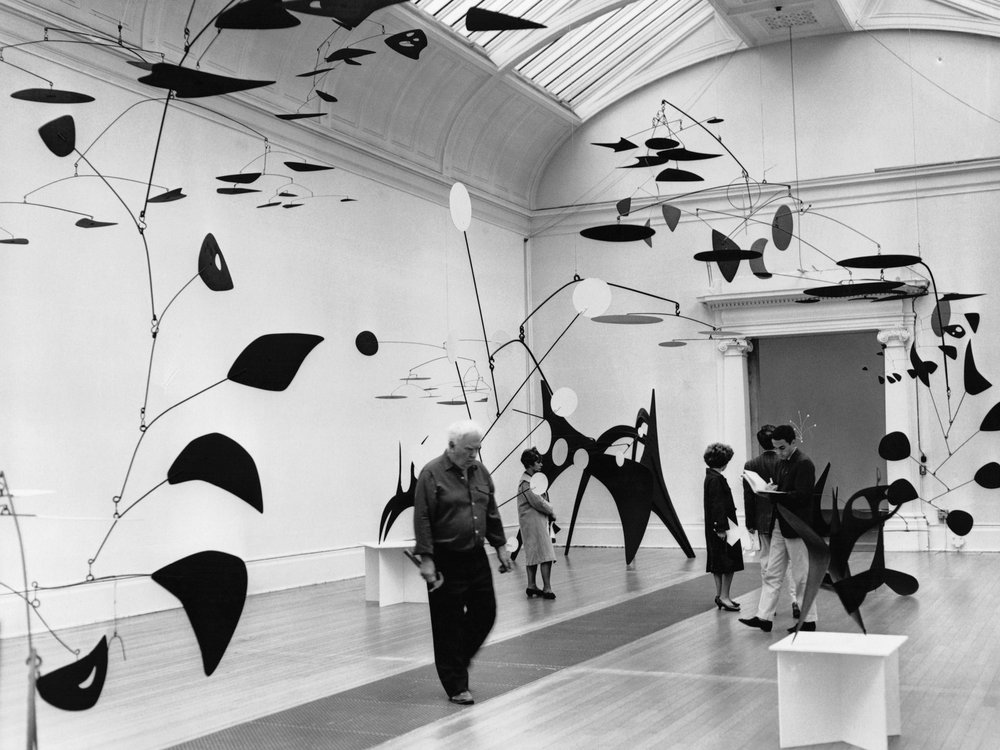 Alexander Calder checks some of his mobiles during a 1962 exhibition of his work at Tate London