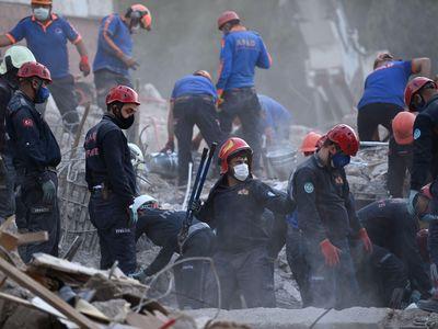 Search and rescue teams search for survivors in the debris of fallen buildings in Izmir, Turkey.