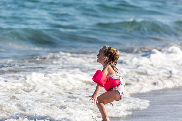 A little girl welcomes the ocean. thumbnail